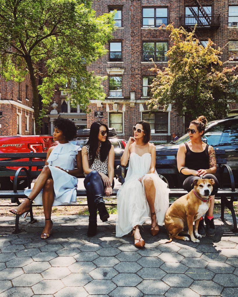 cuatro chicas y un perro en un banco