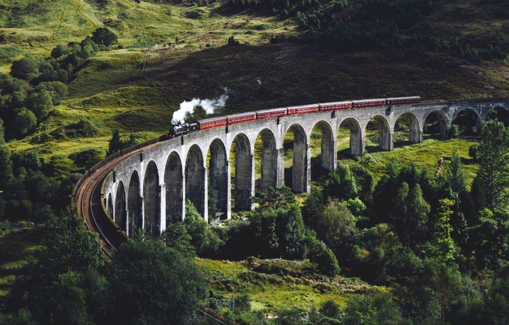 Paisaje verde con tren en Escocia