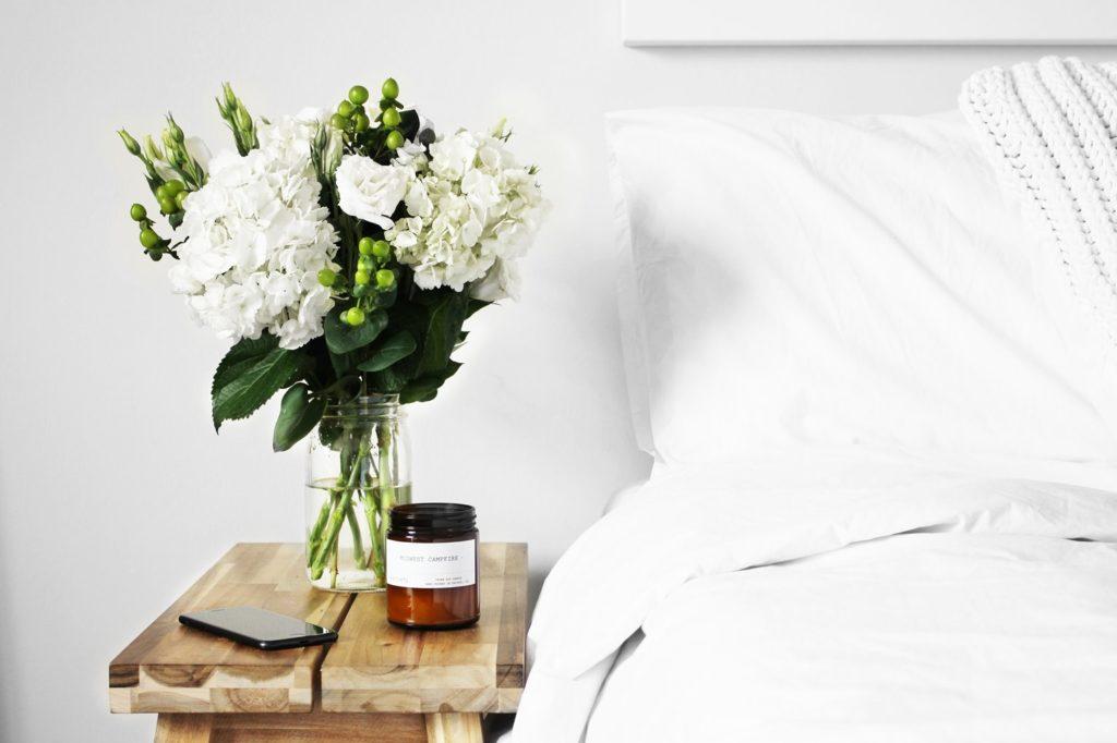 cama y mesilla con flores y vela que es uno de los ambientadores naturales