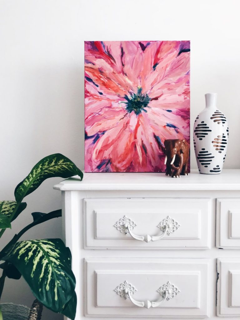 Planta, cómoda y cuadro rosa