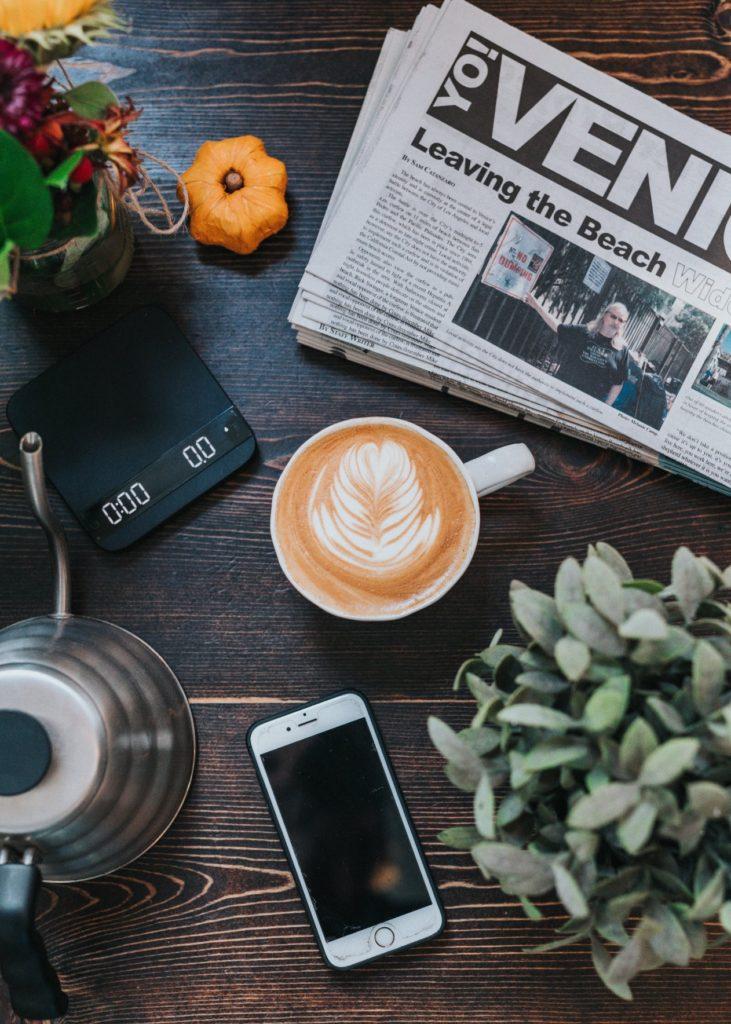 mesa con móvil, café y periódico