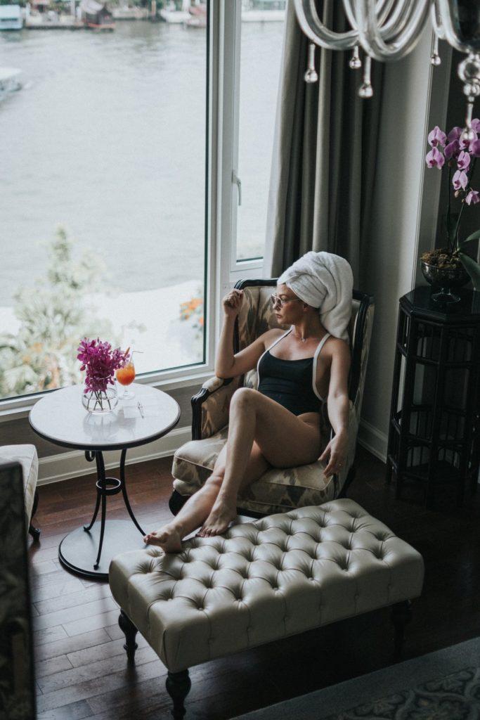 mujer sentada frente a ventana en bañador