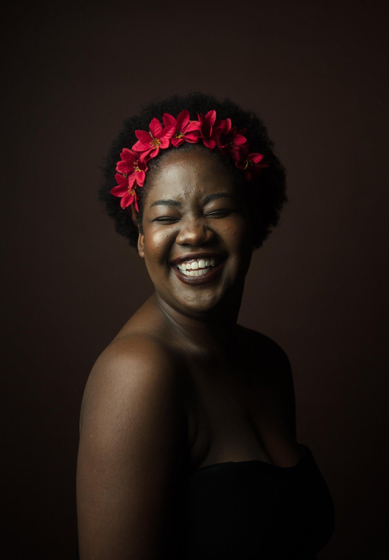 mujer sonriendo con flores rojas en el pelo
