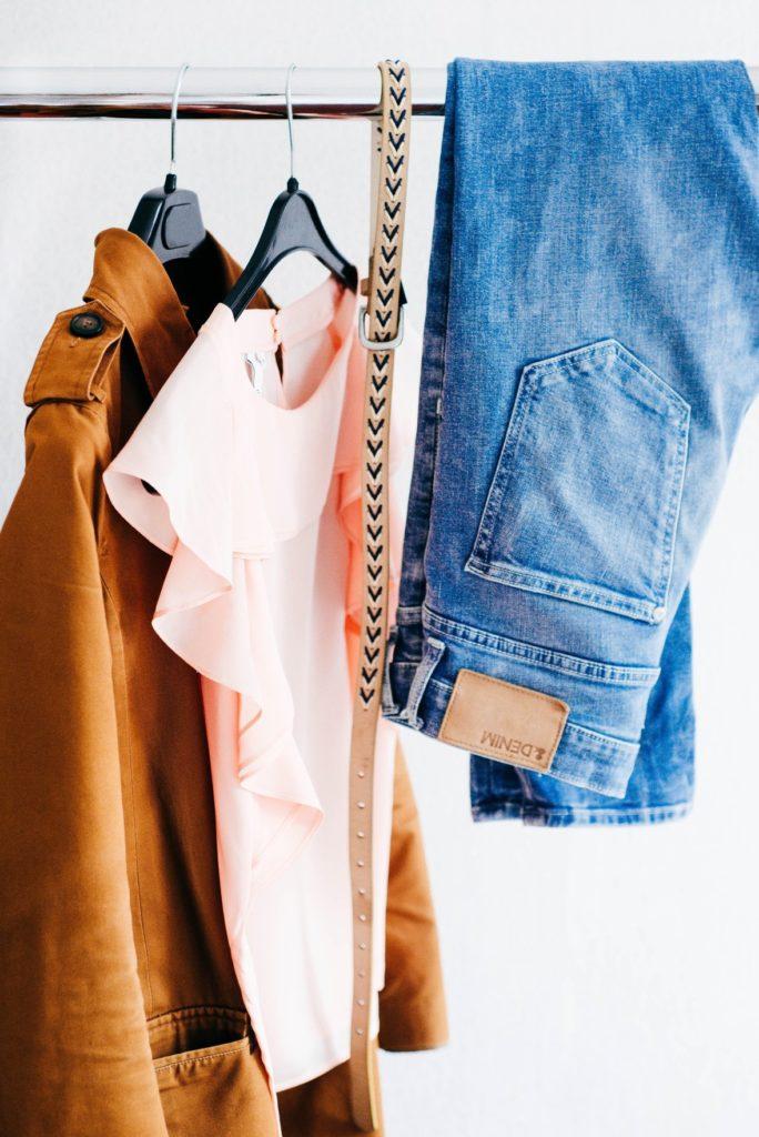 Chaqueta, blusa, cinturón y pantalón colgando de percha