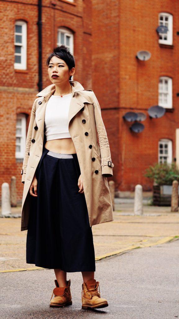 Mujer con falda, top, gabardina y botas