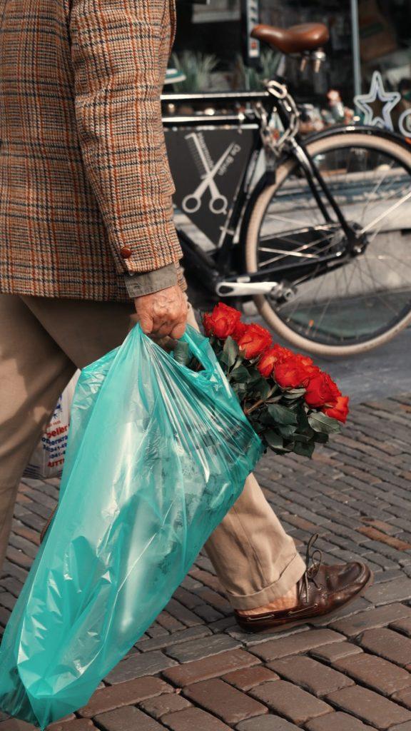 hombre con bolsa de la compra de plástico y rosas